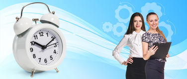 Business women near classical alarm clock. On the blue abstract background stock photo