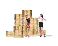 Business women near stack of golden coins. Isolated on the white background royalty free stock photo