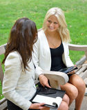 Business women in park together. Two beautiful young business women sit together in an outdoor park bench royalty free stock image