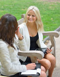 Business women in park together. Two beautiful young business women sit together in an outdoor park bench royalty free stock photos