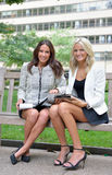 Business women in park together. Two beautiful young business women sit together in an outdoor park bench stock photos