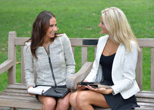 Business women in park together. Two beautiful young business women sit together in an outdoor park bench stock photo