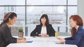 Business women partners actively studying business documents at wooden conference table stock video