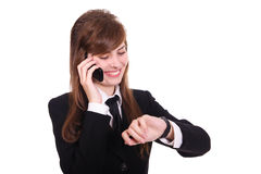 Business women with phone. Business women speaks by phone and looks at the wrist watch Royalty Free Stock Images