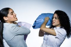Business women pillow fighting Stock Photo