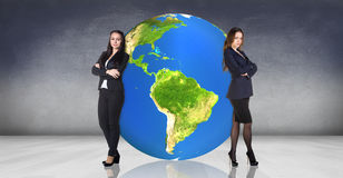 Business women recline on the big earth. Business women stands near big earth ball in the gray room.Elements of this image furnished by NASA Stock Images