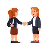 Business women shaking hands, one holding knife. Two business women standing together and shaking each other hands while one holding knife behind her back Stock Photography
