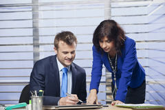 Business women showing coworker where to sign contract. In the office Stock Image