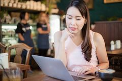 Business women sitting in cafe using laptop and drinking hot coffee stock photos