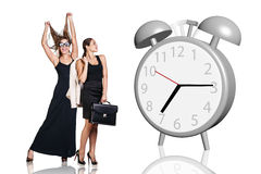 Business women stand near big gray alarm clock. On the white royalty free stock photo