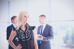 Business woman standing in foreground with a tablet in her hands Royalty Free Stock Photos