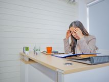 Business women thing about something very serious in her office stock images