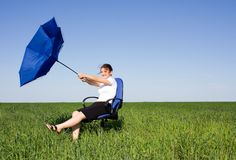 Business women with an umbrella on a grass land Stock Photos