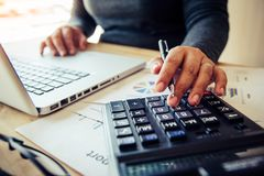Business women are using a calculator to calculate the income of. The business stock photography