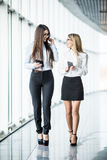 Business women walking and discuss  plans in office hall over panoramic windows. Stock Images