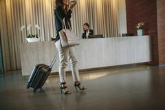 Business woman arriving at hotel hallway with baggage. Business women walking in hotel hallway with his baggage and talking on mobile phone. Female arriving Stock Photo