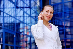 Business women in white with telephone. Business women in white on business architecture background royalty free stock image