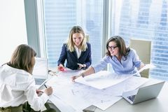 Business women working with business drawings in modern office Royalty Free Stock Photos