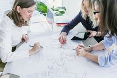 Business women working with business drawings in modern office. Young business women working on business project with drawings at the table in modern office stock image