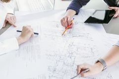 Business women working with business drawings. Women coworkers working together with business drawings on the desk in office stock photos