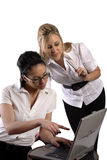 Business women working on laptop. Two business women working on laptop checking reports on the internet, one looking over holding pen Stock Photos