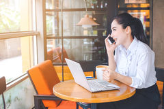 Business women are working on a laptop computer and talking on a Royalty Free Stock Photo