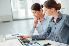 Business women working together on a laptop. Business women at office desk working together on a laptop, teamwork concept Stock Image