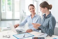 Business women working together on a laptop. Business women at office desk working together on a laptop, teamwork concept Royalty Free Stock Photo