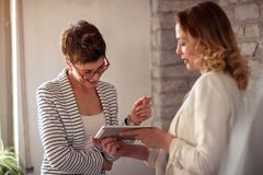 Business women working together looking at tablet royalty free stock images