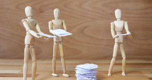 Business wooden figurine standing and holding document. Against wooden background stock video