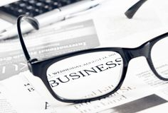 Business word see through glasses lens on financial newspaper Royalty Free Stock Photography