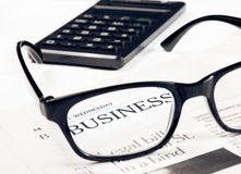 Business word see through glasses lens on financial newspaper near calculator Stock Photography