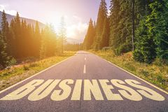 Business word written on road in the mountains.  stock photos