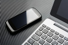 Business Work With Black Smartphone With Reflection Lying Left To A Notebook Keyboard, All Above A Carbon Layer. Business Work With A Black Smartphone With Royalty Free Stock Photo
