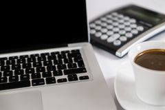 Business work place with cup of coffee calculator and Computer laptop stock photography