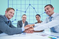 Business workers gather their hands together during a meeting in front of digital screen with graphi Stock Photos