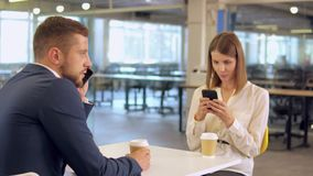 Coffee break at office. Business workers have coffee break. young woman chatting on smartphone drinking coffee. caucasian handsome businessman has phone stock video