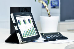 Business workplace. Modern business workplace with digital tablet, calculator, pen and printed data sheet Stock Photo