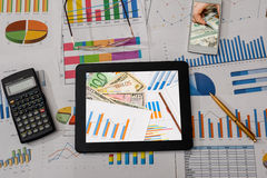 Business workplace with digital tablet, mobile smartphone and some charts and graphs. Pen Royalty Free Stock Photos