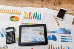 Business workplace with digital tablet, mobile smartphone and some charts and graphs,. Pen Royalty Free Stock Images