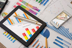 Business workplace with digital tablet, mobile smartphone and some charts and graphs. Pen Royalty Free Stock Image