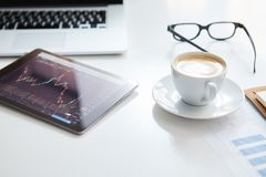 Business workplace with stock market data application on a tablet, banking interface on a tablet and some papers with. Charts, graphs and numbers on a desktop Stock Photo