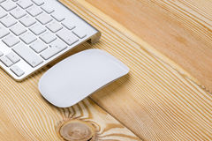 Business workplace with wireless keyboard and mouse on old natural wooden table background. Office desk with copy space stock image