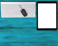 Business Workplace with wireless keyboard, tablet computer and car keys on blue wooden background. Office desk with copy space. Em stock images