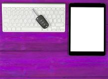Business Workplace with wireless keyboard, tablet computer and car keys on pink wooden background. Office desk with copy space. Royalty Free Stock Photography