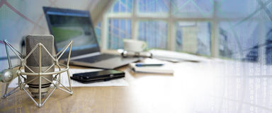 Business workspace for international  journalism with microphone. Laptop, cell phone and notepad on a desktop, panoramic banner with blurred matrix in the Royalty Free Stock Image