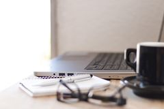 Workspace with a laptop, coffee, notebook, and a glasses. Business workspace with a laptop, coffee, notebook, and a glasses Royalty Free Stock Image