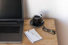 Workspace with a laptop, coffee, notebook, and a glasses. Business workspace with a laptop, coffee, notebook, and a glasses Royalty Free Stock Photography