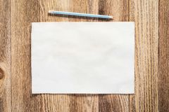 Business workspace with sheet of paper. And pencil lying on wood table. View from above with copy space. Rectangular blank white paper on textured natural royalty free stock images