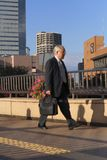 Business world 2. Senior businessman walking in a city. Selective focus on the buildings in the distance, the man is out of focus and blurred. Intended lighting Royalty Free Stock Photo